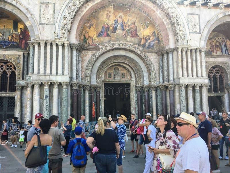 Un grupo grande de turistas fuera de la basílica de las marcas del St en el St marca el cuadrado que toma las fotos y que disfrut fotografía de archivo