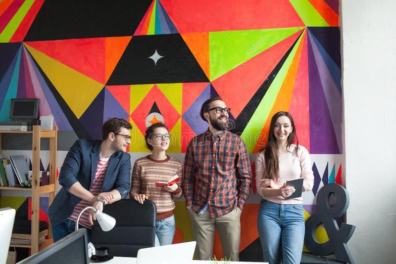 Un gruppo creativo di quattro colleghi che lavorano nell'ufficio moderno fotografia stock libera da diritti