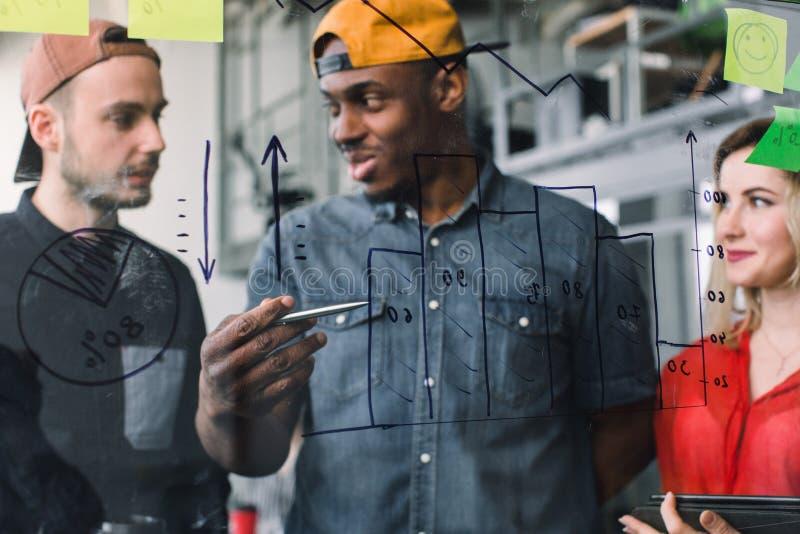 Un gruppo creativo di tre genti di affari multiethnical delle free lance che confrontano le idee sulla parete di vetro in ufficio fotografia stock libera da diritti
