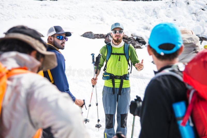 Un gruppo degli scalatori principali da una guida discute l'ascesa imminente immagini stock