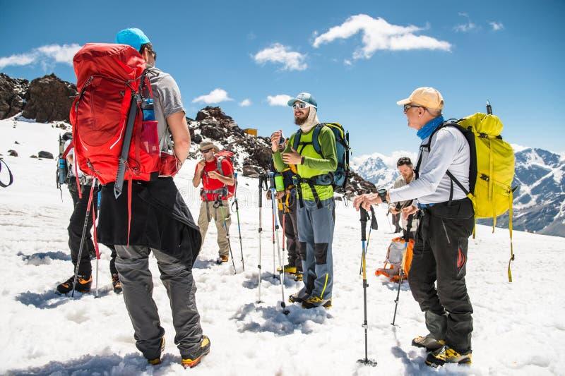 Un gruppo degli scalatori principali da una guida discute l'ascesa imminente fotografie stock