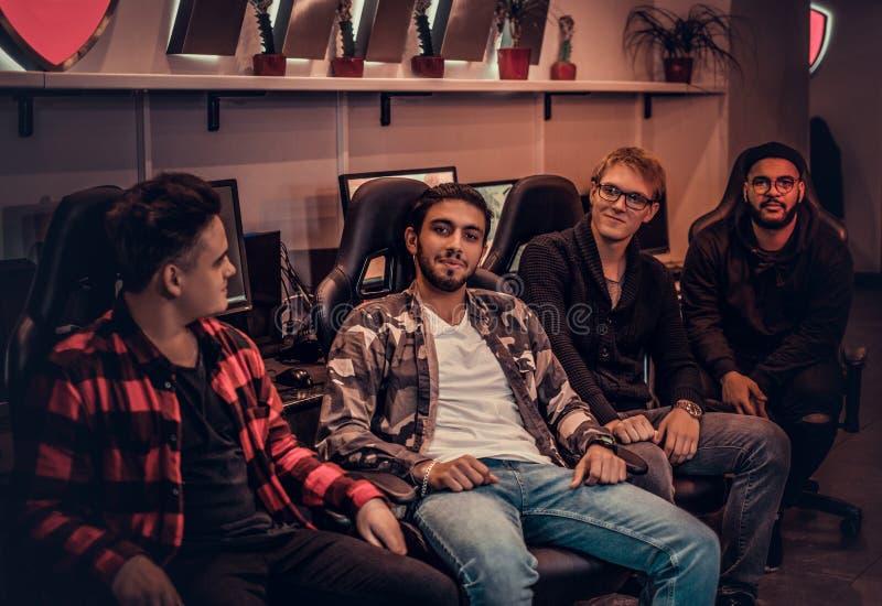 Un gruppo dei gamers adolescenti multirazziali che si siedono sulle sedie del gamer e che esaminano una macchina fotografica in u fotografia stock libera da diritti
