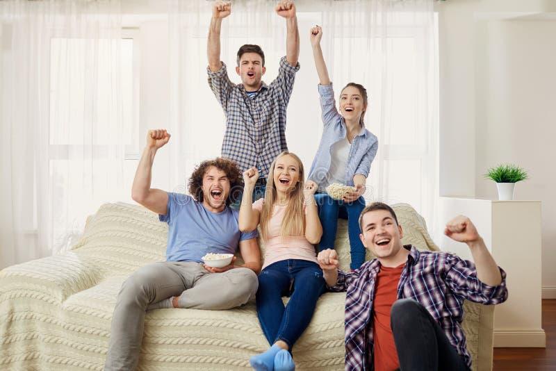 Un gruppo di amici dei fan che guardano gli sport TV che si siedono su un SOF fotografia stock