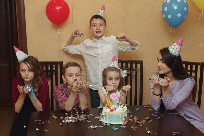 Un gruppo di bambini in cappucci di festa ad un partito del ` s dei bambini I bambini si divertono insieme su una festa della fam fotografia stock