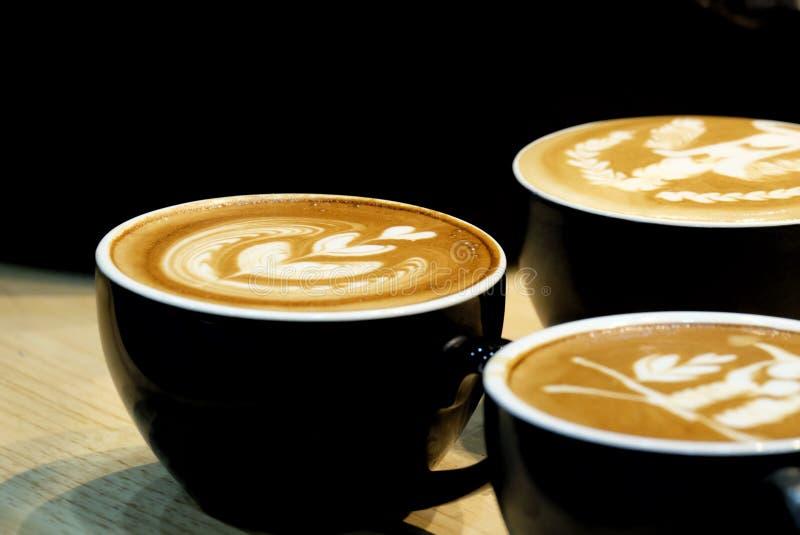 Un gruppo di caffè caldo del latte su una tazza nera con arte del latte sulla tavola dinning superiore e di legno immagine stock