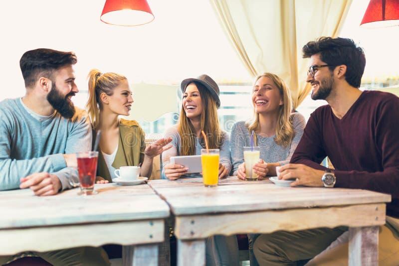 Un gruppo di cinque amici che mangiano un caffè insieme fotografia stock