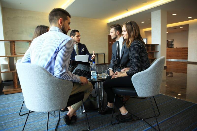 Un gruppo di cinque giovani che discutono qualcosa mentre sedendosi alla tavola nell'ufficio insieme immagini stock