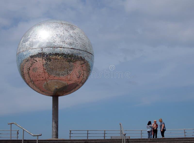 Un gruppo di donne è stato vicino alla palla gigante di scintillio sulla passeggiata di Blackpool con cielo blu e sulla riflessio fotografie stock