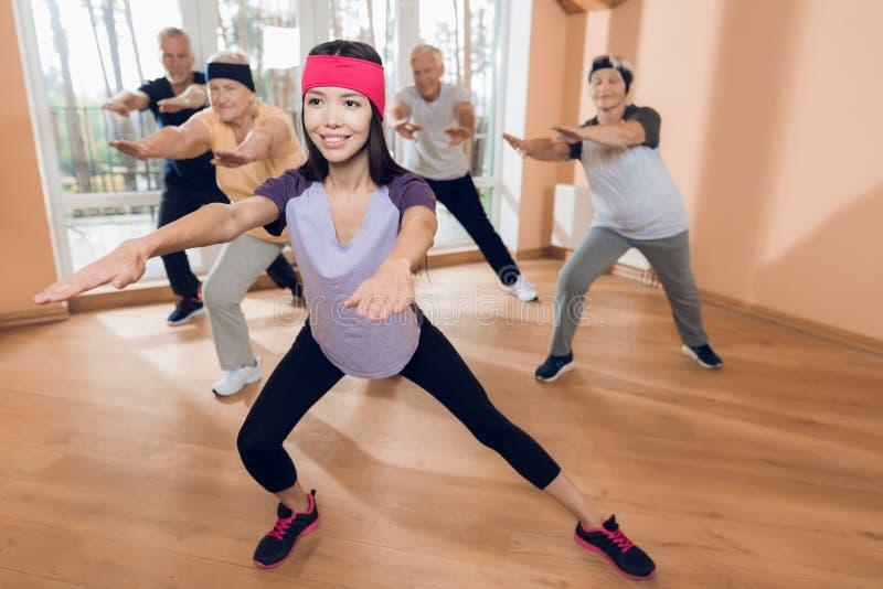 Un gruppo di donne anziane e di uomini che fanno ginnastica terapeutica in una casa di cura immagine stock