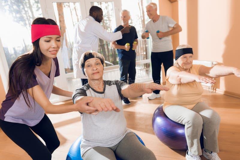 Un gruppo di donne anziane e di uomini che fanno ginnastica terapeutica in una casa di cura fotografie stock libere da diritti
