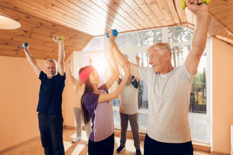 Un gruppo di donne anziane e di uomini che fanno ginnastica terapeutica in una casa di cura fotografia stock