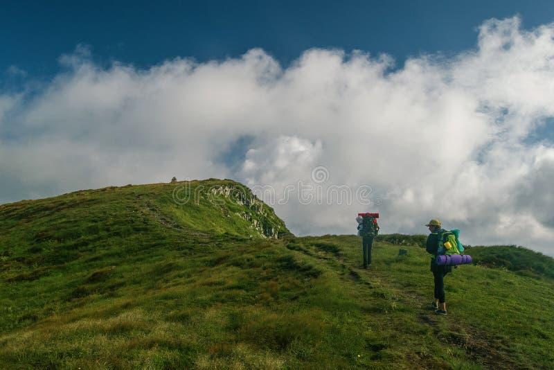 Un gruppo di due turisti scala alla cima della montagna fotografia stock