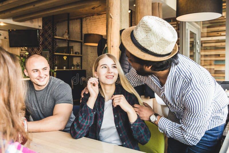Un gruppo di giovani amici allegri sta sedendo in un caffè, le bevande di bevanda, mangiando, selfies della presa e prende le imm fotografia stock libera da diritti