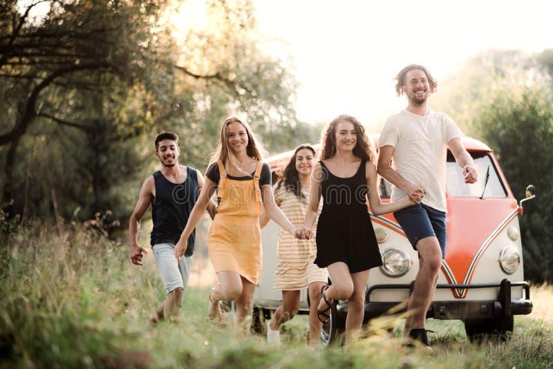 Un gruppo di giovani amici su un roadtrip attraverso la campagna, corrente immagine stock libera da diritti