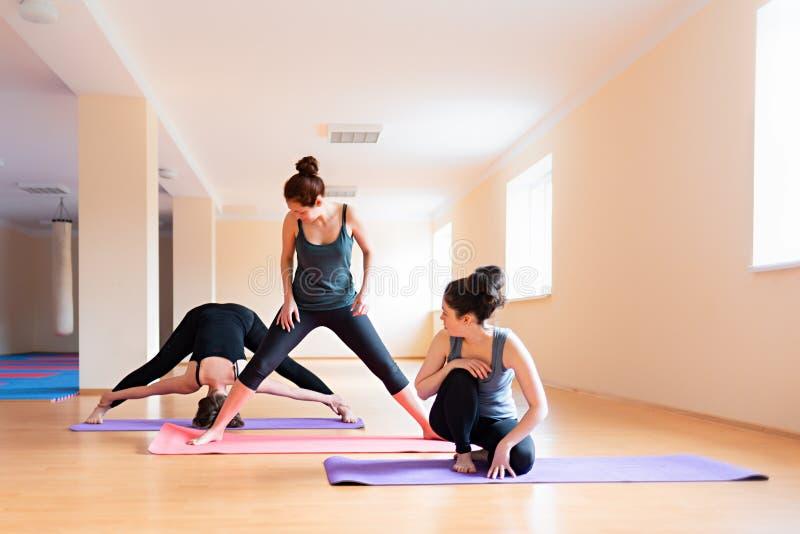 Un gruppo di giovani donne si scalda prima della formazione nella palestra Il concetto dello stile di vita, della ginnastica e de fotografie stock