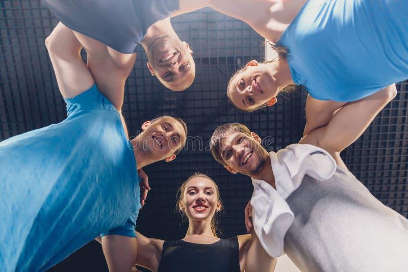Un gruppo di giovani di sport che si abbracciano immagine stock libera da diritti