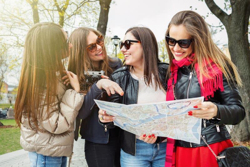 Un gruppo di giovani turisti femminili sta cercando le attrazioni in una citt? europea sulla mappa Quattro allegri e bei immagine stock