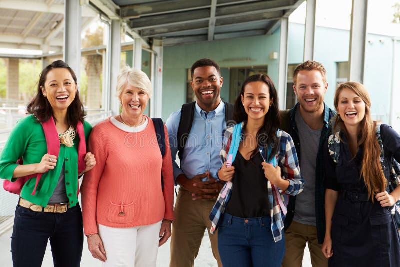 Un gruppo di insegnanti allegri che vanno in giro in corridoio della scuola fotografia stock libera da diritti