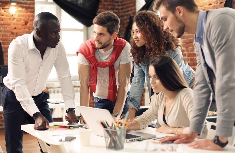 Un gruppo di lampo di genio creativo del lavoratore cinque insieme in ufficio, nuovo stile di area di lavoro, scena felice della  fotografie stock libere da diritti