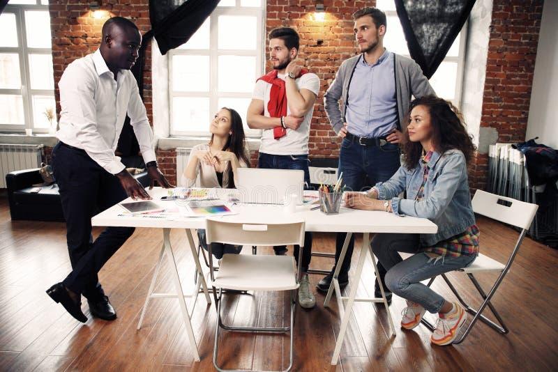 Un gruppo di lampo di genio creativo del lavoratore cinque insieme in ufficio, nuovo stile di area di lavoro, scena felice della  immagini stock libere da diritti