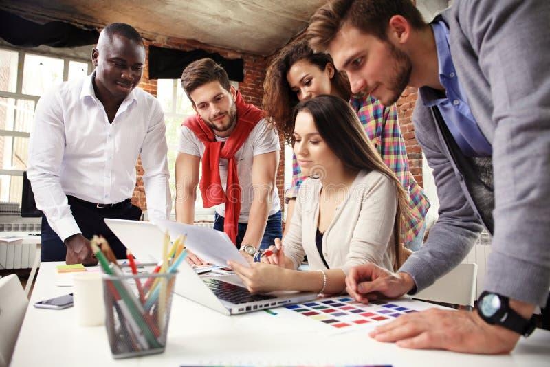 Un gruppo di lampo di genio creativo del lavoratore cinque insieme in ufficio, nuovo stile di area di lavoro, scena felice della  fotografia stock libera da diritti