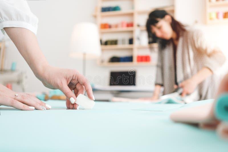 Un gruppo di lavoro di due cucitrici in studio di cucito Piccola impresa Priorità bassa della sfuocatura fotografie stock