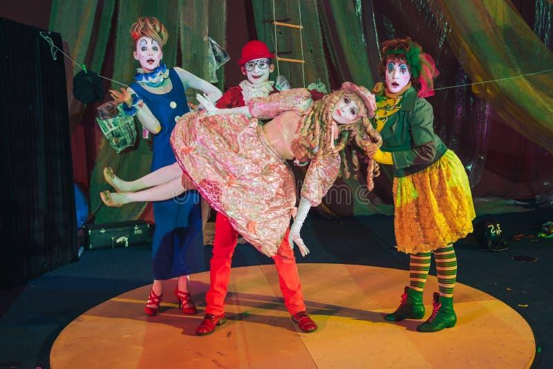 Un gruppo di pagliacci, un uomo del pagliaccio alzato nelle sue armi una donna che ritrae una bambola fissa fotografia stock