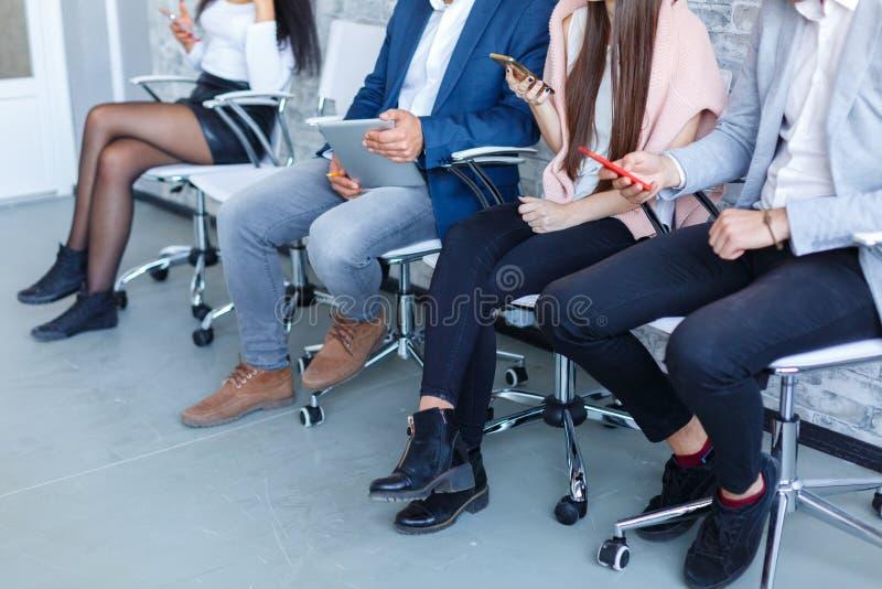 Un gruppo di persone che si siedono in una sala di attesa vicino ad una parete bianca e che per mezzo di un telefono cellulare al immagini stock