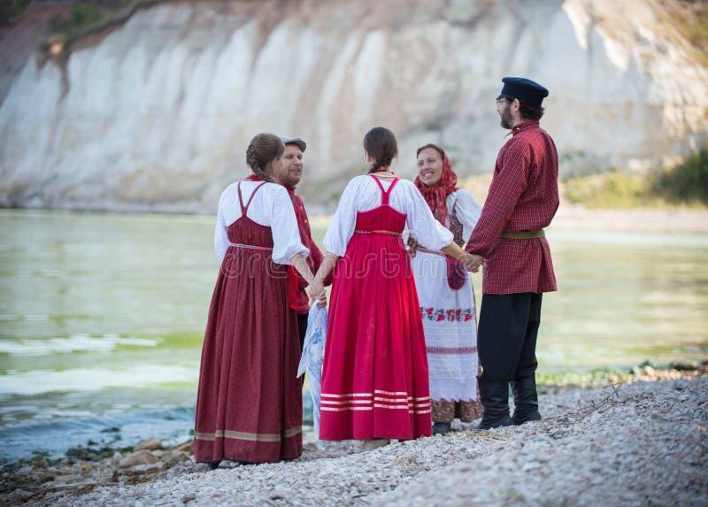 Un gruppo di persone in gente russe costumes il dancing in un bello paesaggio, nella priorità alta è la fisarmonica immagine stock libera da diritti