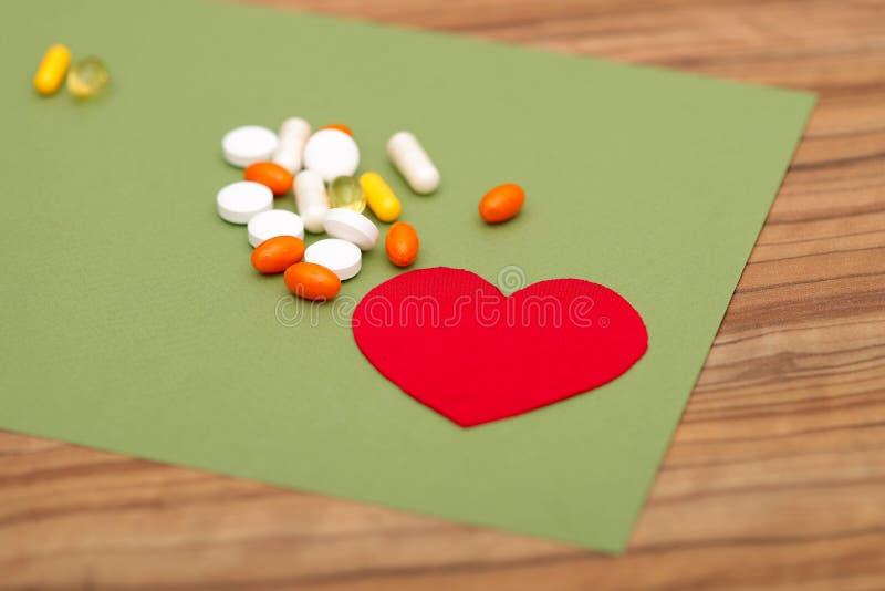 Un gruppo di pillole colorate e un cuore rosso su un fondo verde sulla tavola immagine stock libera da diritti