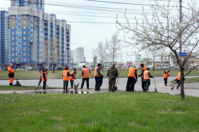 Un gruppo di pulitori delle maglie protettive arancio luminose sta spazzando il marciapiede della città su una via della molla in immagine stock libera da diritti