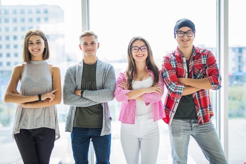 Un gruppo di quattro amici adulti felici che indossano abbigliamento casuale mentre parlandosi in corridoio con la grande finestr immagini stock libere da diritti