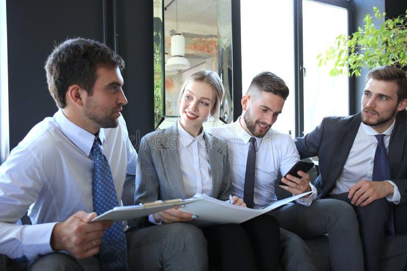 Un gruppo di quattro genti di affari che si siedono sul sof? Non hanno potuto essere più felici circa il lavoro insieme fotografia stock libera da diritti