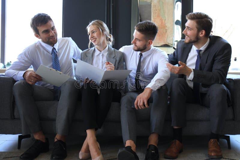 Un gruppo di quattro genti di affari che si siedono sul sof? Non hanno potuto essere pi? felici circa il lavoro insieme immagini stock