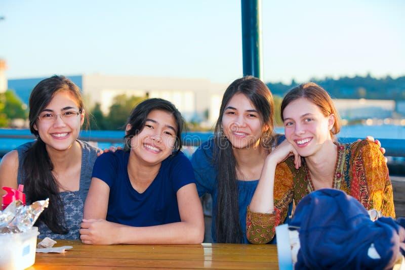 Un gruppo di quattro giovani donne che sorridono insieme dal lago immagine stock