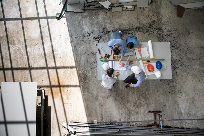 Un gruppo di quattro persone degli ingegneri parla insieme per esaminare il materiale da costruzione ed il lampo di genio circa i fotografia stock libera da diritti