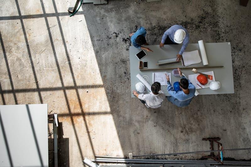Un gruppo di quattro persone degli ingegneri parla insieme per esaminare il materiale da costruzione immagine stock