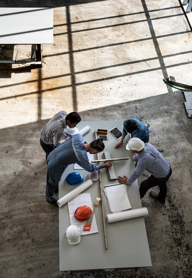 Un gruppo di quattro persone degli ingegneri parla insieme per esaminare il materiale da costruzione fotografia stock libera da diritti