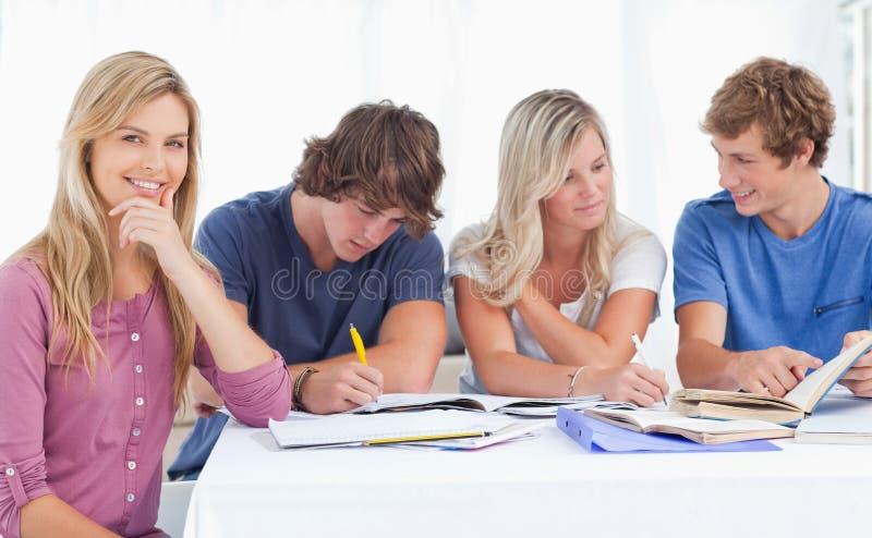 Un gruppo di studio che lavora duro come una ragazza sorride   fotografia stock libera da diritti