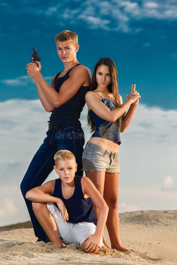 Un gruppo di tre adolescenti sugli sguardi utili della spiaggia La SK fotografie stock libere da diritti