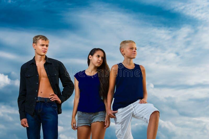 Un gruppo di tre adolescenti sugli sguardi utili della spiaggia La SK fotografia stock