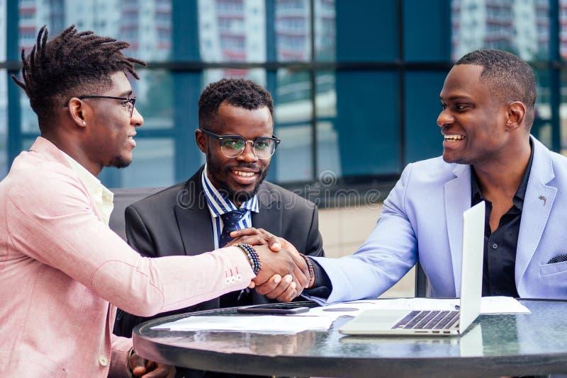 Un gruppo di tre eleganti uomini d'affari afro-americani amici imprenditori di moda si riuniscono a fotografia stock