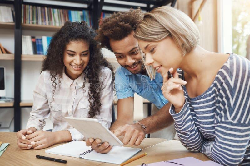 Un gruppo di tre giovani belli startupers che si siedono nello spazio coworking della luce, parlando del progetto futuro, guardan immagini stock libere da diritti