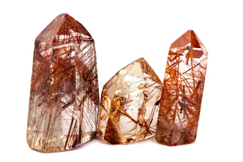 Un gruppo di tre rocce minerali del quarzo con il rutilo isolato su un fondo bianco fotografia stock