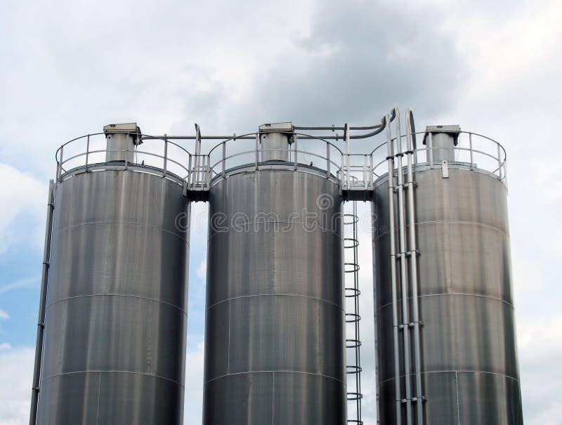 Un gruppo di tre serbatoi chimici d'acciaio alti con i tubi di collegamento e di scale contro un cielo nuvoloso blu fotografia stock libera da diritti