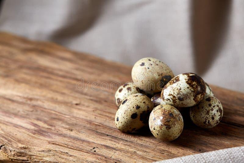 Un gruppo di tre uova di quaglia sul pezzo di legno sopra la tovaglia homespun, vista superiore, fuoco selettivo, lampadina fotografie stock