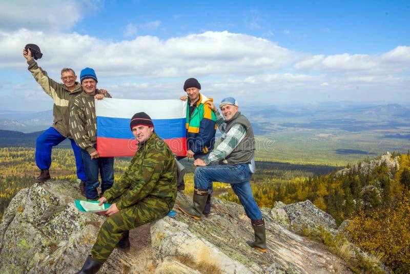 Un gruppo di turisti alla cima della montagna Yalangas nei Urals del sud con la bandiera nazionale russa fotografie stock libere da diritti