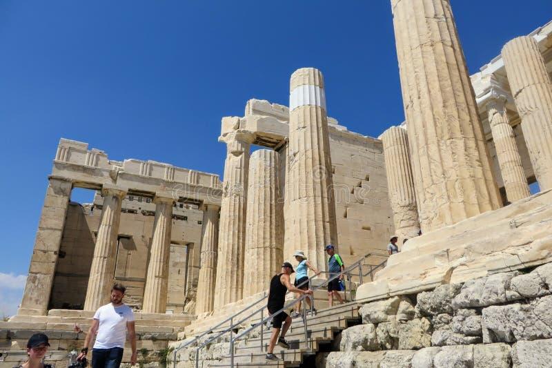 Un gruppo di turisti che entrano nell'acropoli che cammina attraverso le colonne doric di marmo massicce un giorno di estate sole fotografie stock libere da diritti