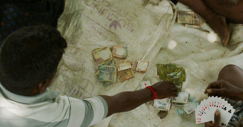 Un gruppo di uomini indiani gioca le carte sulla via in India fotografia stock