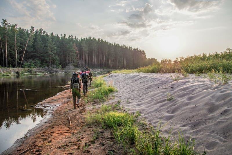 Un gruppo di viandanti con gli zainhi viaggia vicino al fiume nella zona di Cernobyl fotografia stock